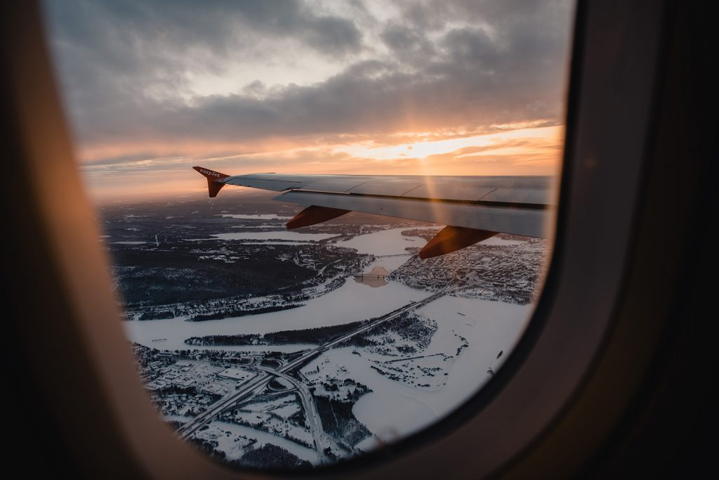 Plane flying over snowy Finland at sunset