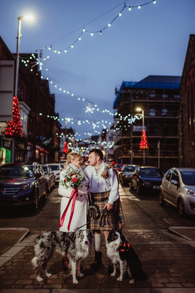 Newlyweds with their dogs with Christmas lights in Douglas